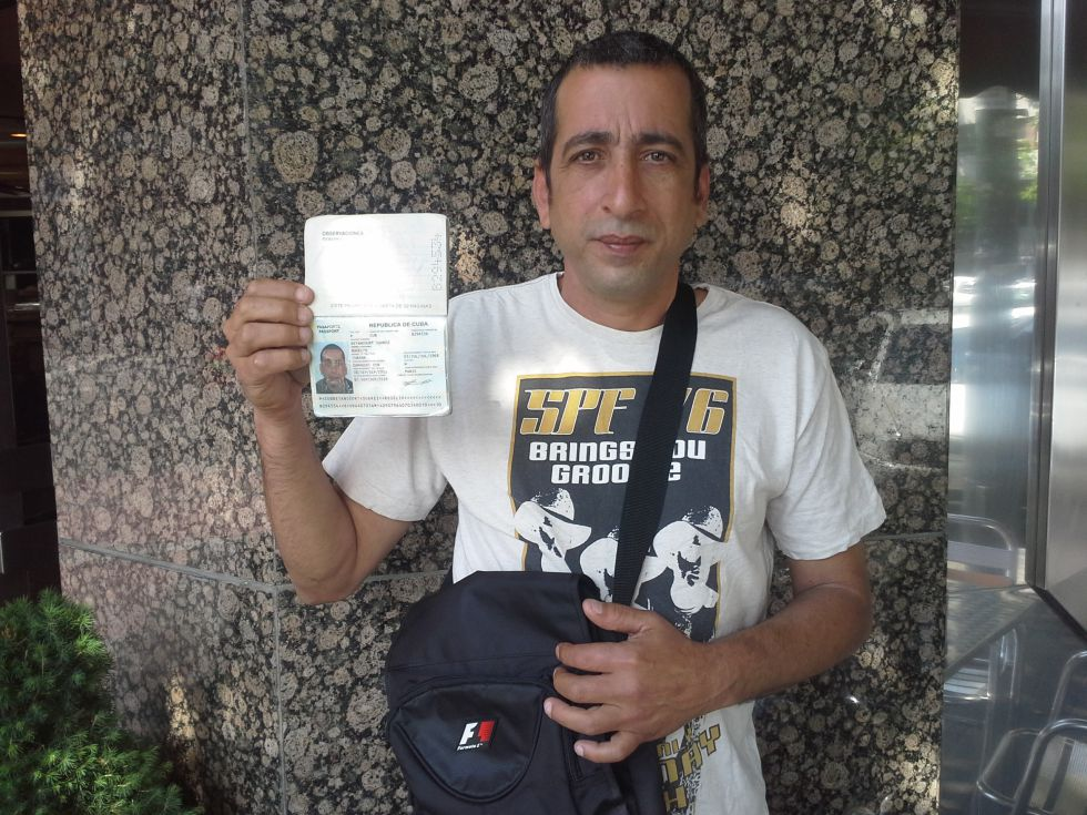 Rogelio Betancourt muestra su pasaporte en un café de la plaza de Castilla en Madrid, junio de 2014. / M. G.-R.