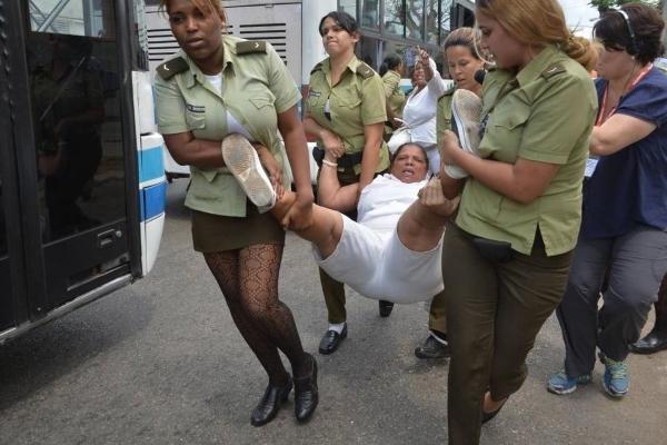 Una Dama de Blanco es cargada en peso en La Habana por mujeres oficiales del Ministerio del Interior. Foto tomada del portal Cubanet.